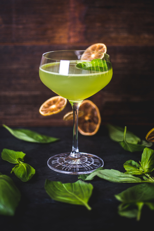 Cocktail on the background of falling lemon slices.