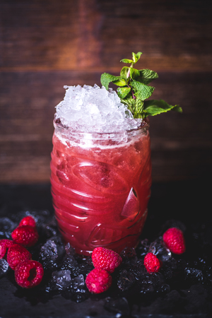 Raspberry cocktail with ice and mint is on the table. Фото со стока