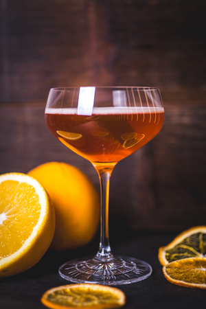 Oranges are reflected on the glass of a glass with a drink.