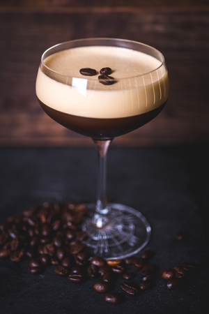 Coffee beans lie on the foam of the coffee cocktail. Фото со стока