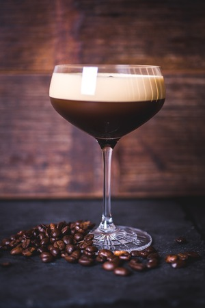 A coffee cocktail stands on a wooden background.