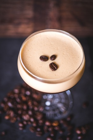 Top view of the coffee beans lying on the foam cocktail.