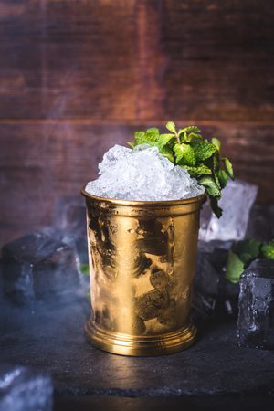 A tin can with ice is decorated with a sprig of mint.