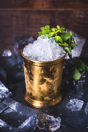 A small iron bucket stands on a table with ice. Archivio Fotografico