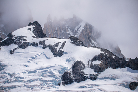 The snow will cover the top of the mountains. The fog envelops the top of the rocks. Sunlight reflects on the rocks.