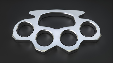 Chrome knuckle duster in a simple black studio space. Stock Photo