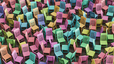 cor: A large array of colorfully stained wooden chairs facing random directions and tightly packed. This image is a 3D illustration. Stock Photo