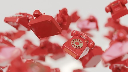 Floating swarm of retro red rotary phones on a seamless white background. This image is a 3d render and features a shallow depth of field. Stock Photo