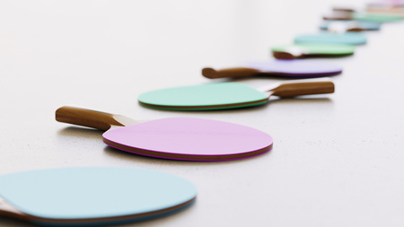 Neat line of variously oriented table tennis paddles on a modern minimalist neutral surface. This image is a 3d rendering.