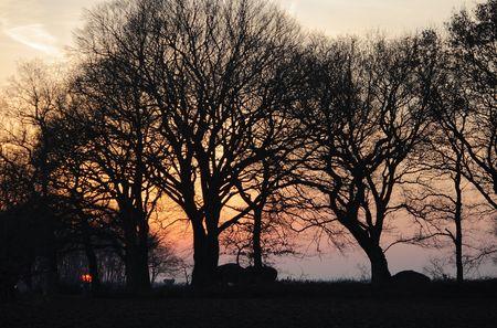 neolithic: Paisaje puesta de sol con siluetas de dos tumbas de �poca neol�tica 3000 AC Foto de archivo