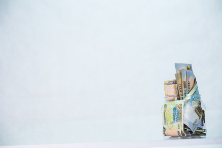 Local currencies and Naira notes in a glass jar - concept of Saving Stock Photo - 124280987