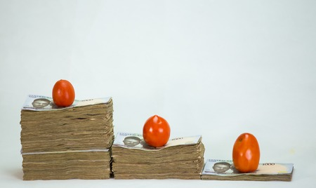 Stack of nigeria naira notes on white background wit tomatoes