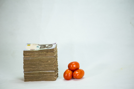 Stack of nigeria naira notes and tomatoes - increase in food commodity Stock Photo
