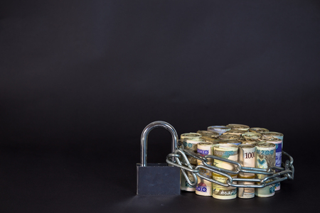 Bundles of naira cash chained and padlock concept of Esecurity on black background Stock Photo - 124281274