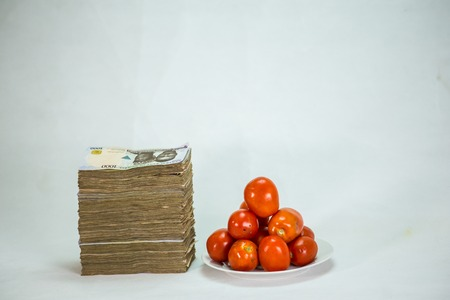 Stack of nigeria naira notes on white background wit tomatoes Stock Photo - 124281297
