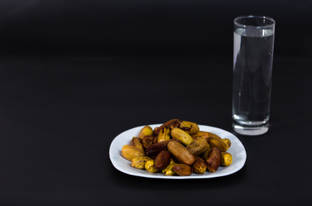 Nigeria local dates with glass of water on black background