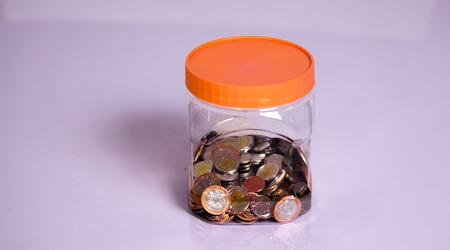 coins and Savings in a transparent bottle Stock Photo