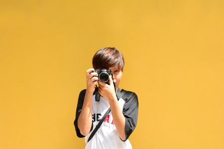 Photographer on yellow wall. photo