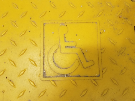 yellow wheel chair symbol on rough surface