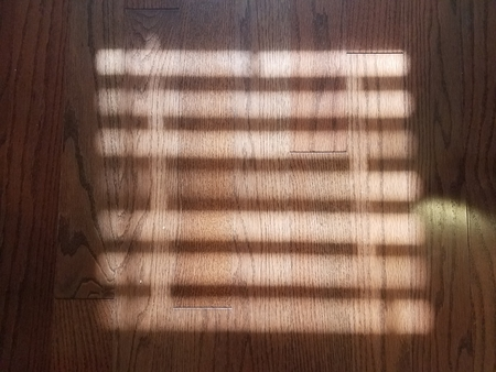 sunlight shining on dark wood floor through window blinds Stock Photo