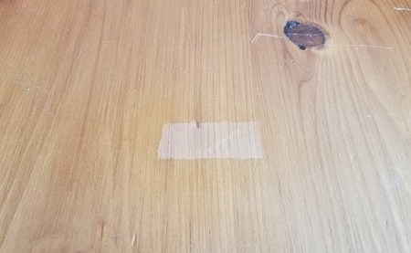 brown wood table or surface with place where tape had been