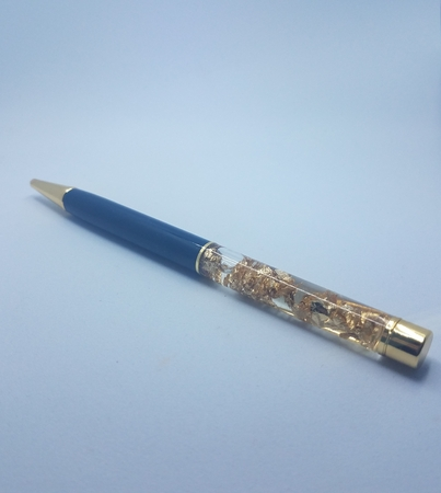 pen with gold flakes or nuggets on white background