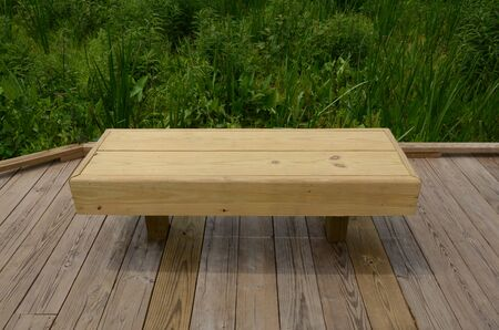 wood bench or seat on boardwalk with green plants