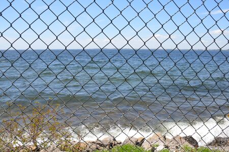 metal chain link fence with ocean or sea water and sky