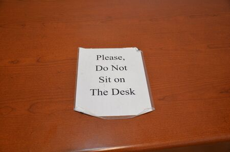 please do not sit on the desk sign on brown wood desk