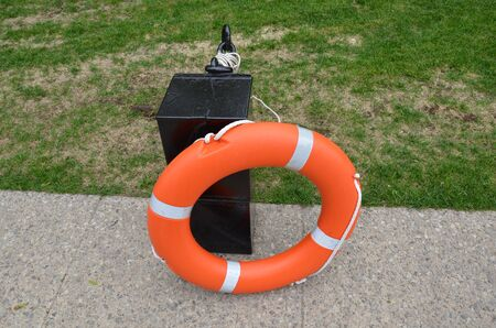 circular orange life preserver on sidewalk with green grass