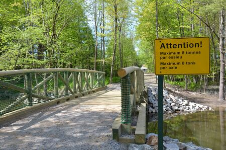 yellow attention maximum 8 tons per axle sign in French and English on bridge