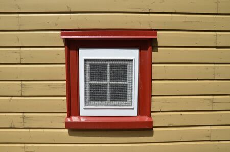red and white window on brown wood building or structure