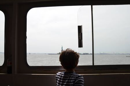boy child on ferry on river looking through window to Statue of Liberty and Ellis Island