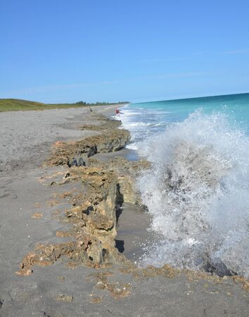 blue ocean water splashing on dirty rocks on the beach 版權商用圖片