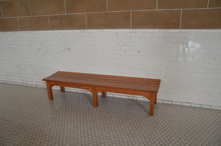 brown wood bench with hexagon floor tiles and rectangle white wall tiles Stock Photo