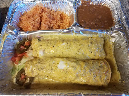 enchiladas with green sauce and rice and beans in metal tray