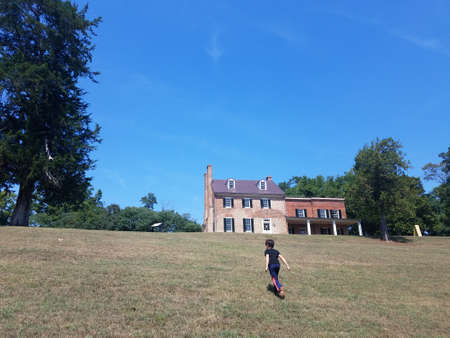 child running up hill or grass with building