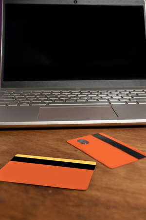 credit cards in front of laptop on wooden table