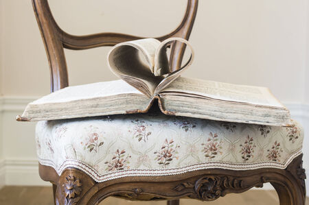 Pages of open book rolled in heart shape on the chair
