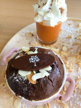cup cakes: Chocolate Mug Cake with almond in a cup on wood plate
