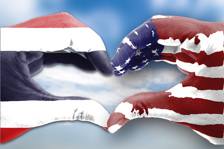 female human hands in heart shaped of the United States with Thailand flag pattern on bright blue sky background with clouds