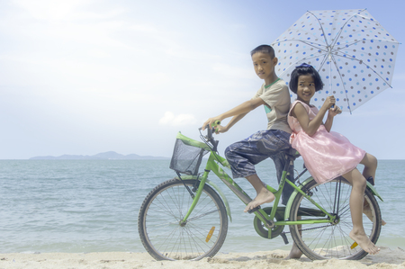 Happy little girl and boy ride bicycle playing on the beach. Stock Photo