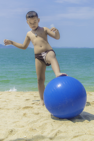 Little boy with ball playing on the beach. Stock Photo