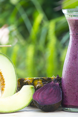 Glass of beet juice on wooden table in the garden, closeup