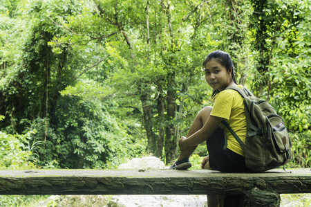 Travel and freedom. Young woman with backpack enjoying tropical waterfall view.