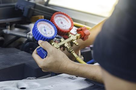 Auto mechanic uses a pressure gauge on the air compressor,liquid air pressure,compressor,manometer in a car,Selective focus.