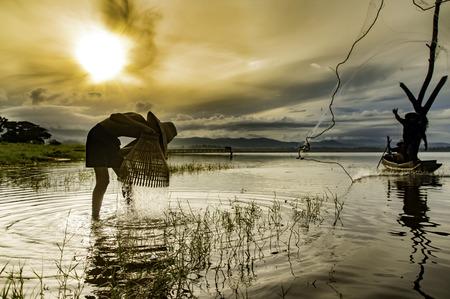 Vroege ochtend vissersboot, Vissers en jong geitje die in het vroege ochtend gouden licht op de boot, de Cloundy hemel en de waterachtergrond, Noordelijk van Thailand vissen.