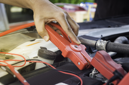 Auto mechanic uses a charging battery with electricity trough jumper cables in a car,Selective focus.