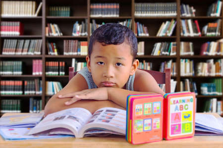 Portrait of asian kid reading student in a library,Education concept.