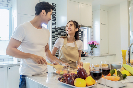 Asian young couple is looking and smiling while cooking in kitchen at home. Couple helping mixing salad.
